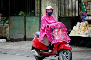 a local woman riding in the rain in North Vietnam