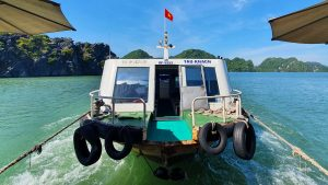 little boat being tugged behind a bigger one in Ha Long Bay, near Cat Ba Island