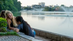 a local and a foreigner conversing by the lake