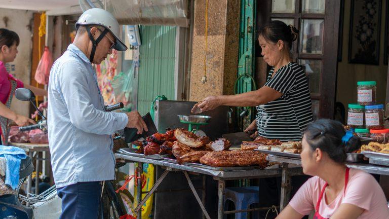 a man buying roast pork in Hanoi's Old Quarter
